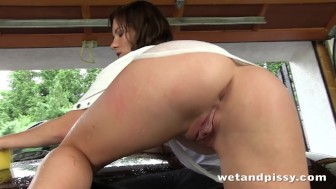 Gorgeous brunette uses her golden piss to clean her car with