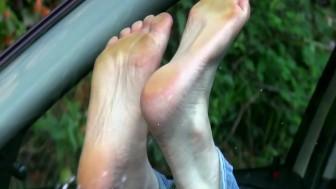 Bare feet against windshield