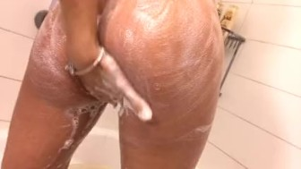 The beautiful woman soapes herself with foam and is played with her fingers