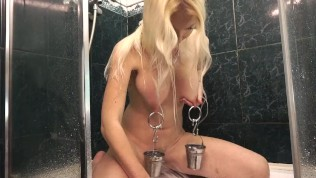 Hot blonde with buckets on the nipples masturbates in the shower