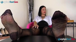 Brunette in black pantyhose gives herself a foot massage